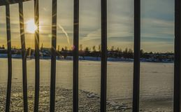 Sun flares through the railing and reflection on the frozen river royalty free stock images