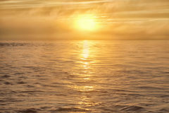 The sun in the fog over the sea. The sky and the water reflects golden sunlight Stock Image