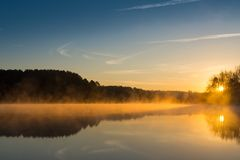 Sun, Fog Reflecting Off Lake at Dawn Stock Photography