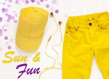 Yellow flatlay jeans, baseball cap and headphones summer background card,top view.Sun and fun background