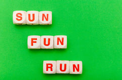 Sun Fun Run. Still life with dices and the word sun fun and run, green background Stock Photos