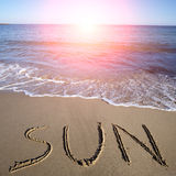Sun geschrieben auf nassen Sand Stockfotografie