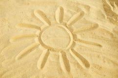 Sun gezeichnet in den Sand Stockbild