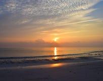 Sun giallo dorato che aumenta all'orizzonte con il cielo variopinto con la riflessione in spiaggia acqua di Kalapathar del mare,  fotografia stock