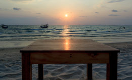Sun glade on top of wooden table at sunset with seaview background Royalty Free Stock Images