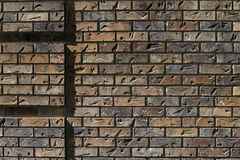 Sun glances off a brick wall with impressions giving it texture background Royalty Free Stock Photography