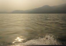Sun glare in lake Garda. Mountains in the mist. Sepia effect stock photography
