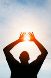 Sun Glaring through Hands of Silhouetted Man. Sun glaring through the silhouetted hands of a man, standing against a cheerful, blue sky stock photo