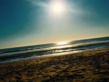Sun glaring over beach. The sun glaring over a beach with earthy sand royalty free stock image