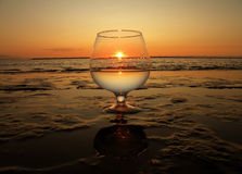 The sun in a glass. Glass at sea coast and in it a sunset Royalty Free Stock Photography