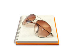 Sun glass Placed On Note Book Cover Orange Stock Image