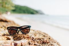 A sun glass put on the rock at the beach. In sunny day of vacation time Royalty Free Stock Photos