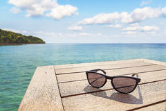 Sun glass at seaside and nice sky. Black sun glass on wood terrace at seaside with nice blue sky Stock Image