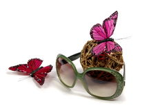 Sun glasses. Still-life from sun glasses with pastes, the butterfly and a gold ball Royalty Free Stock Photography