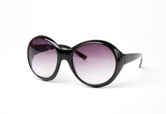 Sun glasses. Female sun glasses in a black frame and lilac lenses on a white background close up royalty free stock photos