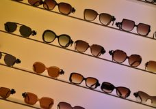 Sun-glasses. On a lightened display shelf Stock Photos