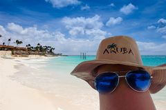 Sun glasses and Aruba hat on a leg. Eagle beach on background royalty free stock photography