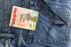 Sun glasses on blue jeans. Stock Photos