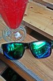 Sun glasses & Cocktail - smartphone selfie. Sun glasses with glossy green shades and an icy cold red alcoholic cocktail sitting on a wooden pallet table royalty free stock image