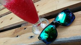 Sun glasses & Cocktail - smartphone selfie. Sun glasses with glossy green shades and an icy cold red alcoholic cocktail sitting on a wooden pallet table royalty free stock images