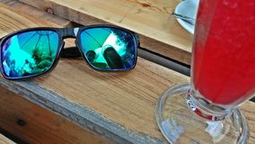 Sun glasses & Cocktail - smartphone selfie. Sun glasses with glossy green shades and an icy cold red alcoholic cocktail sitting on a wooden pallet table Stock Photos