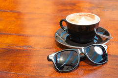 Sun glasses and coffee outside on wooden table Royalty Free Stock Image