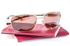 Sun glasses on foreign passport. Gold sun glasses on red passport for travelling abroad royalty free stock photos
