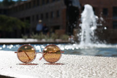 Sun glasses in front of water fountain. Pink sun glasses in focus with water fountain in the background Royalty Free Stock Photography