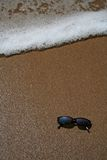 Sun glasses in the sand at the beach. With an approaching wave royalty free stock photos