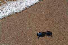 Sun glasses in the sand at the beach. With an approaching wave royalty free stock images