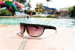 Sun glasses by the swimming pool royalty free stock image