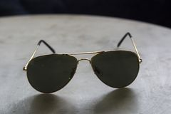 Sun glasses on the table. Dark sun glasses on the marble table royalty free stock images