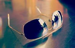 Sun glasses on wood table Stock Photos