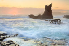 Sun glimpses over the horizon at Cathedral Rock Kiama Stock Photography