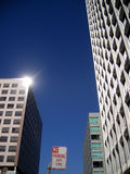 Sun glinting off modern office building. The sun is reflected off the side of a modern downtown office building with a no parking sign in the forground Stock Photos