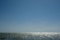 Sun glinting off the ocean surface. With a lone sailboat in view Stock Photo