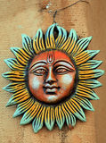 Sun god. Wall-hanging of sun god face in outdoors stock images