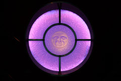 Sun God stained glass window. A stained glass window of a sun god in purple glass stock photo