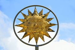 Sun God symbol against blue skies. Golden sun god symbol on metal rod against blue skies with clouds on sunny day stock photos