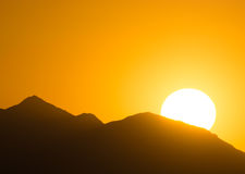 Sunset over mountains in the desert. The sun goes down behind mountains in the Arizona desert Royalty Free Stock Photography