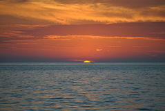 Sun goes down. A sunset as it's going down over the lake,looking like it's inside lake royalty free stock image