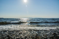 The sun goes down to the sea, the waves on coast in sunny patches. Many solar glare Stock Photography