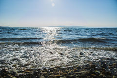 The sun goes down to the sea, the waves on coast in sunny patches Stock Images