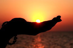 Sun in hand. Sun set captured in hand. Hand in silhouette and sun as if resting on hand Royalty Free Stock Photos