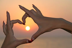 Sun in hands. Sunset background Royalty Free Stock Images