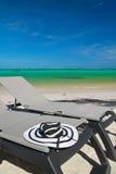 Sun hat on beach chaise longues Stock Photos