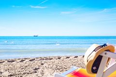 Sun hat on the deck chair on the beach. Colorful beach chairs and sun hat on the beach, vacation. Traveler dreams concept Stock Images