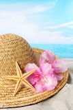 Sun hat and flowers on the beach Stock Photography