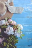 Sun hat and flowers on blue wooden plank background. Holiday and relax concept. Pastel tone. Accessory, beach, brim, brown, clothes, clothing, copy, craft stock image