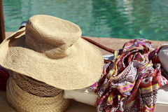 Sun hat and pareo in front of a swimming pool Stock Images